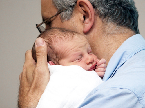 Grandfather holding a newborn baby